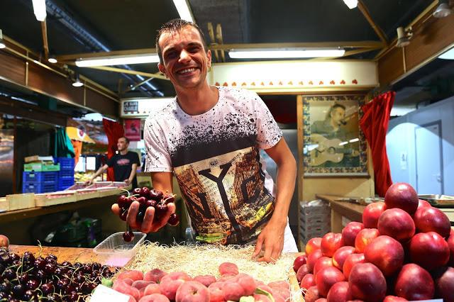 fruit seller, Sète market, languedoc, france. George Brassens in background