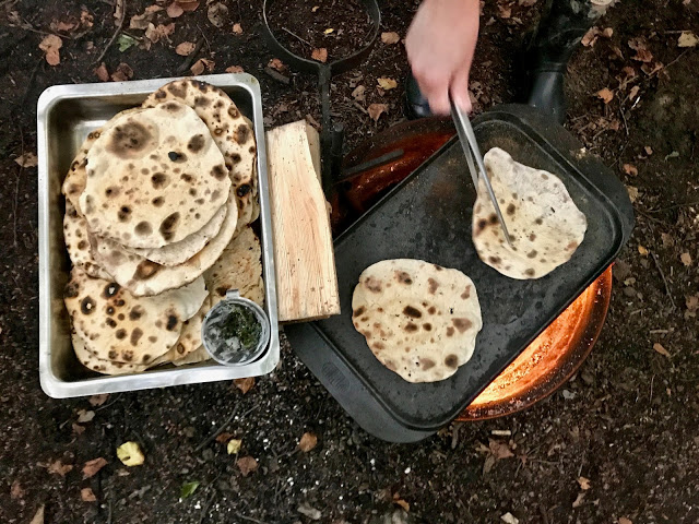Cooking flat breads on the fire, pure food camp, Skane, Sweden